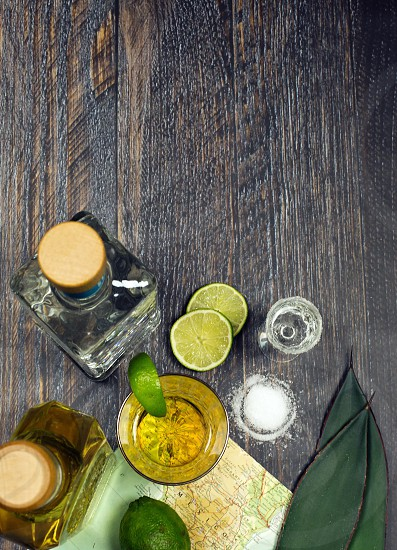 tequila blanco reposado agave leaves salt limes Mexico map wood surface shot glass bottles photo