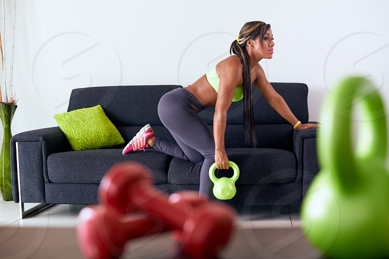 woman fitness workout raising weight wellness shoulders 20s active african american athlete attractive beautiful black body bodycare clothing copy space domestic exercise exercising female full length girl green holding home house indoor lifestyle muscular one people person pretty raise rowing shoulder sitting slim sofa sport sports sportswear train training weightloss working out young photo