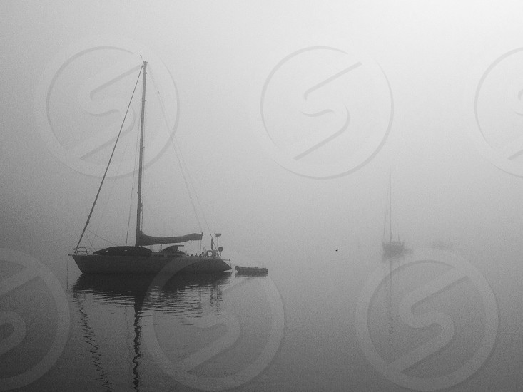 white sailboat on water grayscale photography photo
