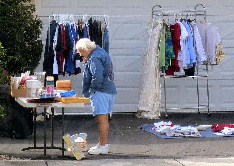 Garage sale lady browsing table of goods racks of clothing photo