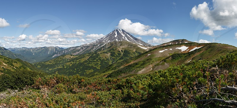Panorama: beautiful summer mountain landscape on Kamchatka Peninsula - picturesque view of Vilyuchinsky Volcano at sunny day. Photo stratovolcano photographed with Vilyuchinsky Pass (Russian Far East) photo