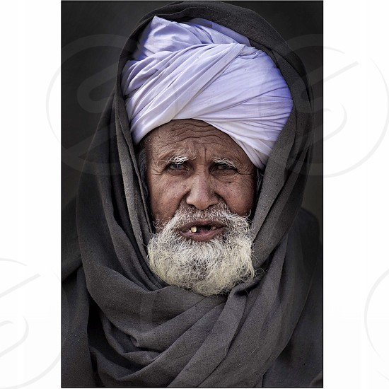 man in purple turban and black coat photo