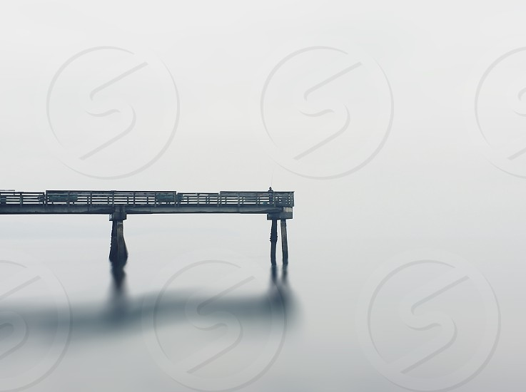 large dock out in water in complete fog photo