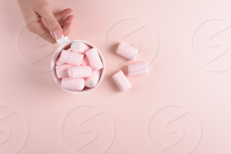Feminine hands holding hot chocolate with marsmallow candies on pink paper background. Top view. Copy space photo