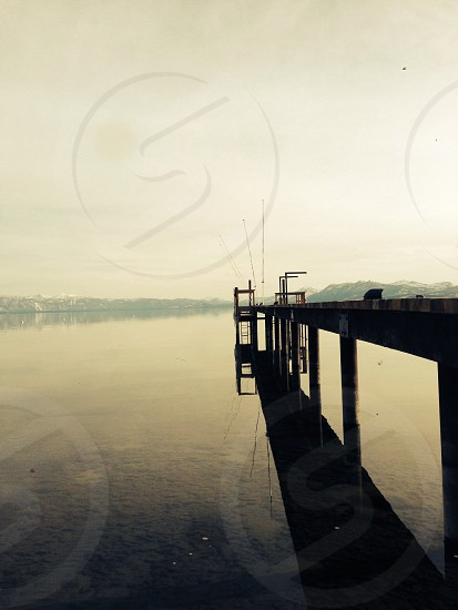 mountain across unfinished dock over water during day photo