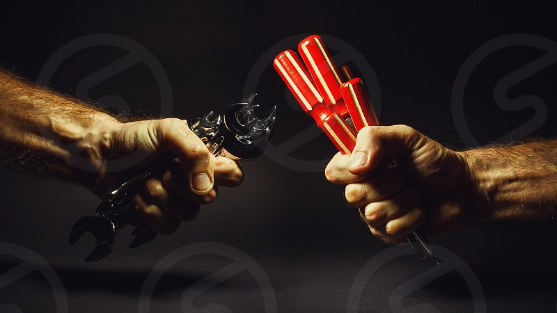 Two male hands are holding set of screwdrivers and wrenches. photo
