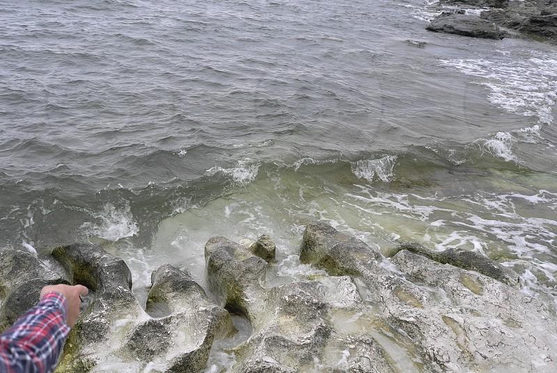 plaid arm pointing ocean sight limestone waves rocks photo