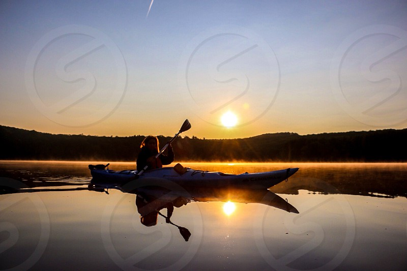 person riding canoe on body of water during sunset photo