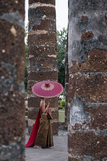 women in traditional dress at the Wat Mahathat Temple at the Historical Park in Sukhothai in the Provinz Sukhothai in Thailand.   Thailand Sukhothai November 2018 photo