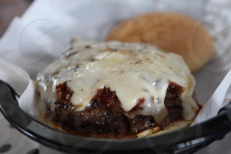 Burger patty with melted white cheese photo