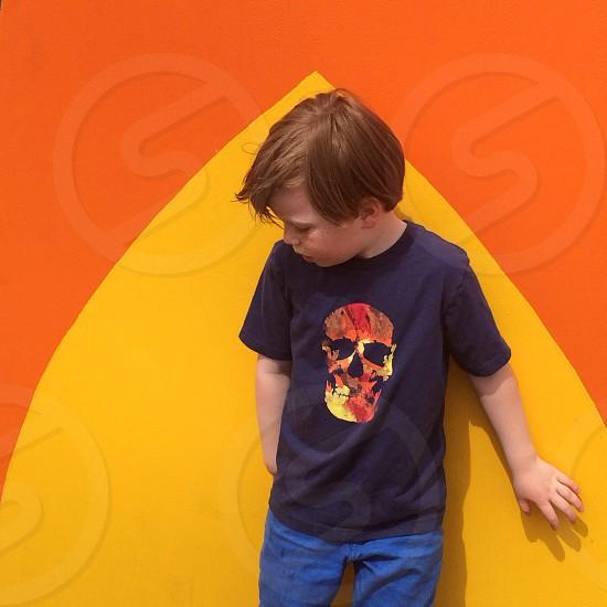 kid wearing blue crew neck t-shirt with orange skull print photo