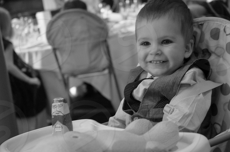 baby boy smiling at a wedding photo