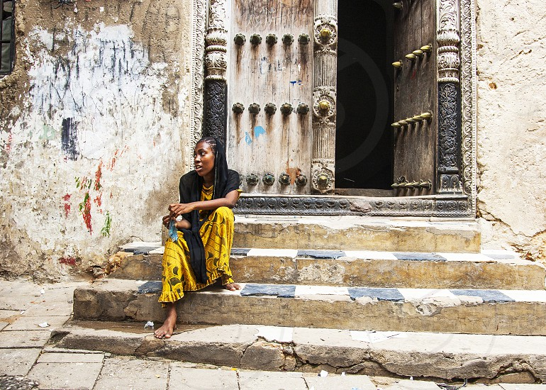 Girl sitting on a staircase in Stone Town Zanzibar Tanzania photo