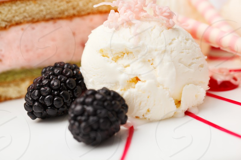 Scoop of vanilla ice cream with blackberries served with a berry cake drizzled with fruit syrup photo
