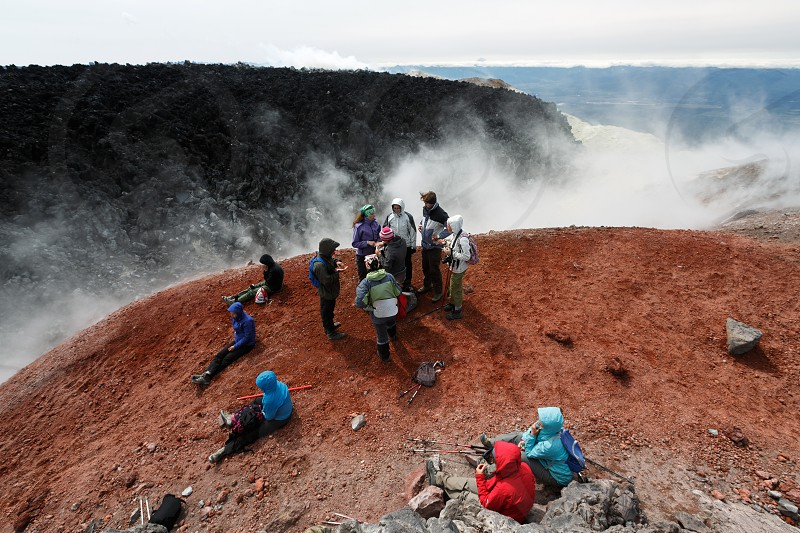 AVACHA VOLCANO KAMCHATKA PENINSULA RUSSIAN FAR EAST - AUG 7 2014: Large group of tourists and travelers rests in crater of active Avachinsky Volcano after hours of climbing to the top of volcano. photo