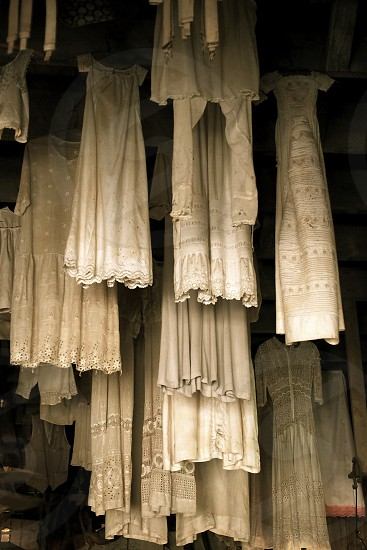 Antique dresses hanging. Vertical. White. Lace.  photo