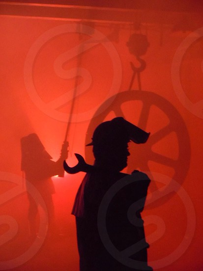 silhouette of man carrying open wrench photo
