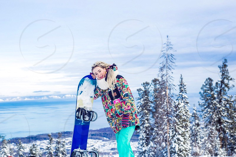 woman in teal pink and black clothes leaning on blue snowboard near on pine tree covered in snow under gray cloudy sky during daytime photo