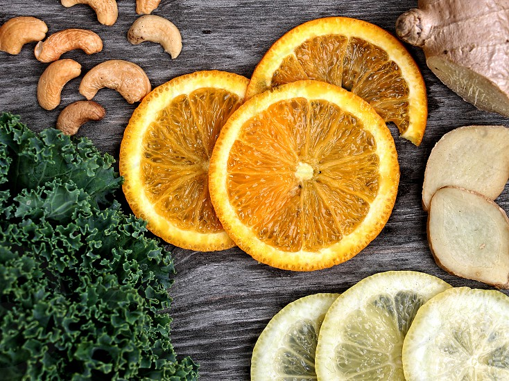 Aerials still life of healthy foods including oranges lemons cashew nuts kale and ginger photo