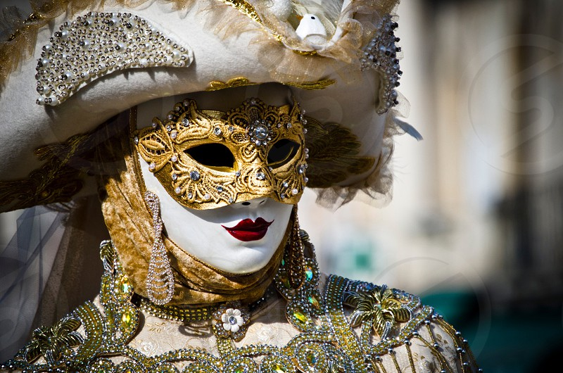 person in white mask and gold costume with hat photo