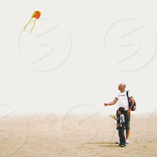 Man and boy flying a kite on the cloudy beach photo