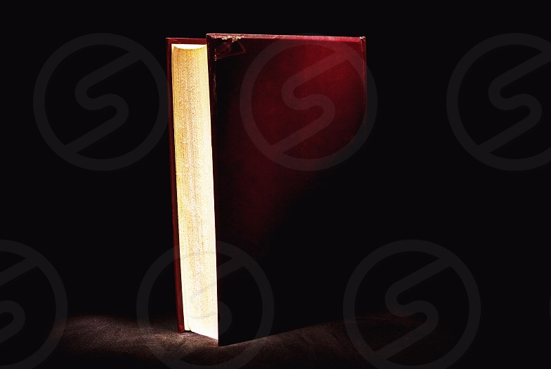 Closeup view on old red book in the dark. photo
