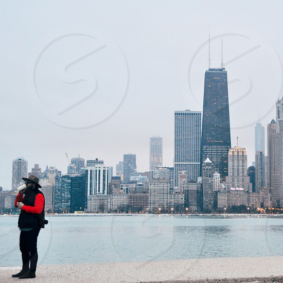 man in red long sleeved shirt wearing brown hat with city building across background photo