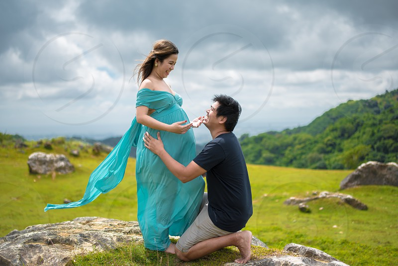pregnant woman in teal off-shoulder dress standing near kneeling man in black t-shirt under gray cloudy skies photo