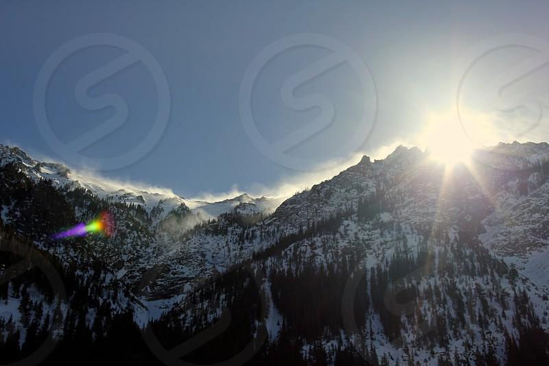 Sun peeking over the snowy Colorado mountains in the spring of 2014 photo