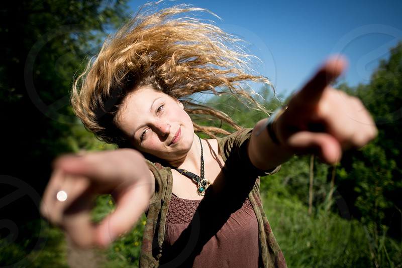 Pretty alternative girl pointing fingers outward and flipping and whipping her hair photo