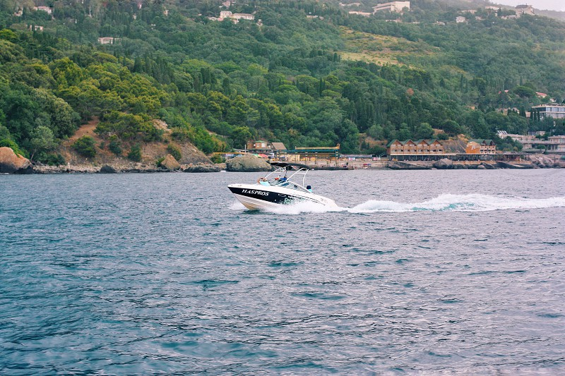 blue and black speedboat in sea during daytime photo