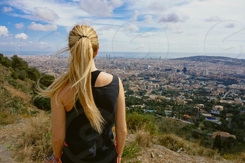 woman with long blonde hair in ponytail on mountain overlooking city in black tank top photo