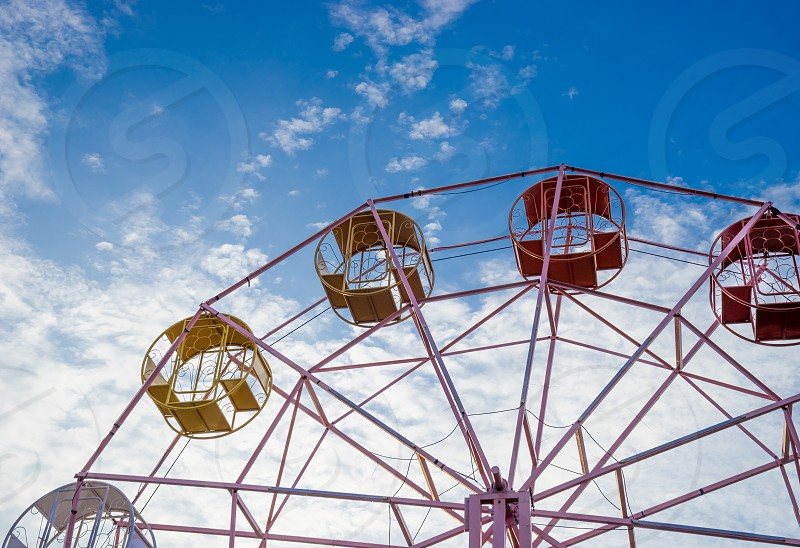 close up part of pastel ferris wheel on blue sky photo