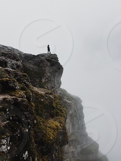 person standing atop a grey rocky cliff photo