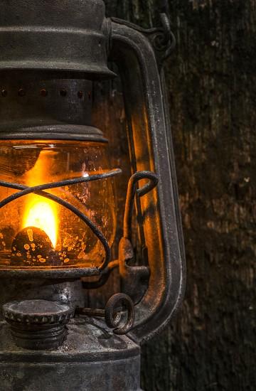 Old gas lantern on wood at darkness photo