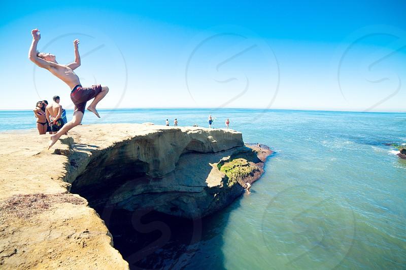man jumping on beach photo