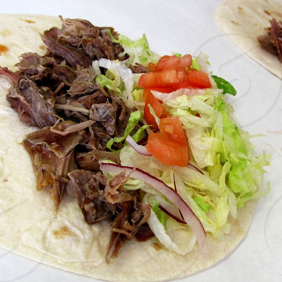 Shredded goat meat with tomato lettuce and onion on tortilla photo