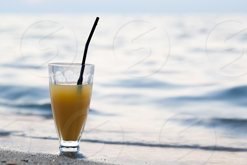 Close-up shot of glass of cocktail or fruit juice with straw standing on beach close to sea. Summer vacation photo