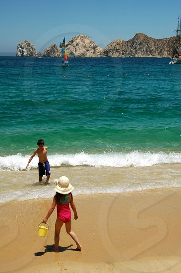 two kids playing in sandy beach on sunny day photo
