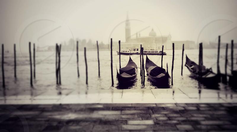 Black and white of gondolas in Venice rain. photo