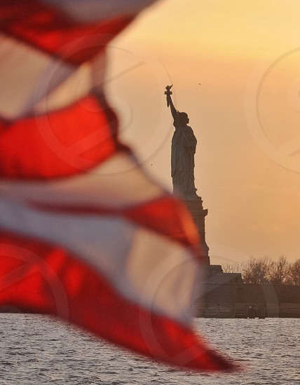 red and white flag and statue of liberty across the body of water under orange sunset photo