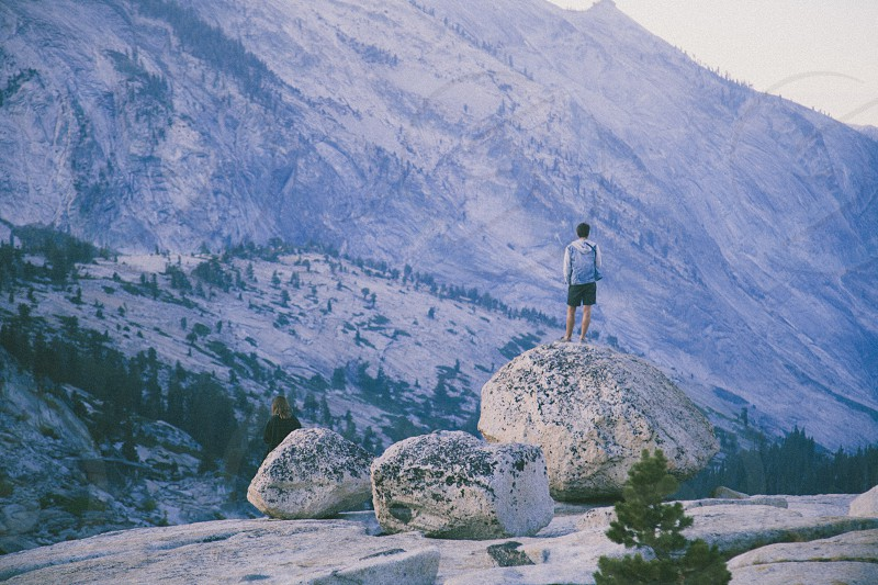 man standing on large rock by the cliff photo
