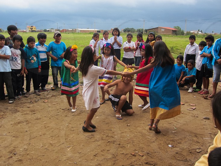 girls forming a circle and dancing with boy in the middle photo