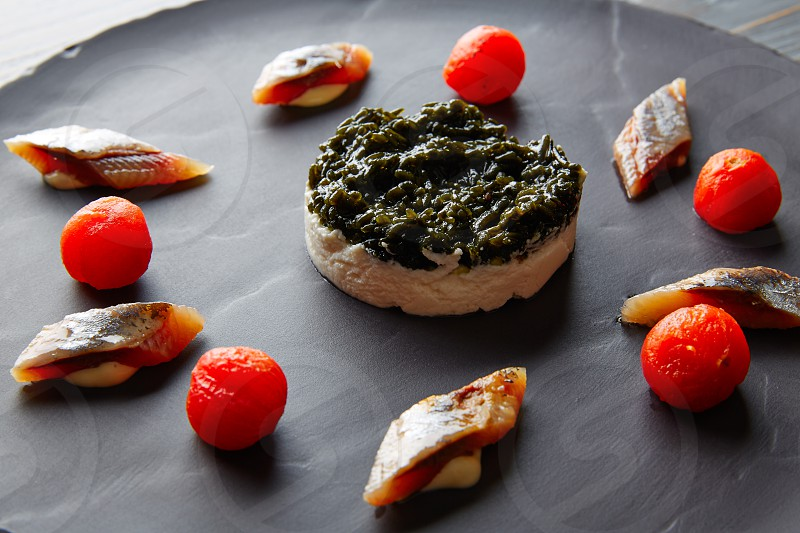 Bota sardine with white garlic pannacotta codium and osmotized tomatoes photo