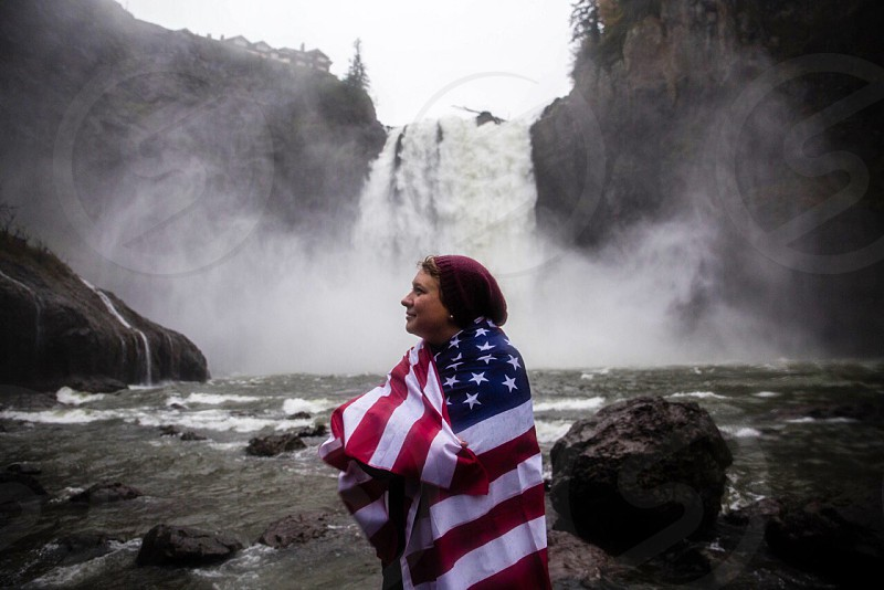 person in red beanie standing in front of water falls photo