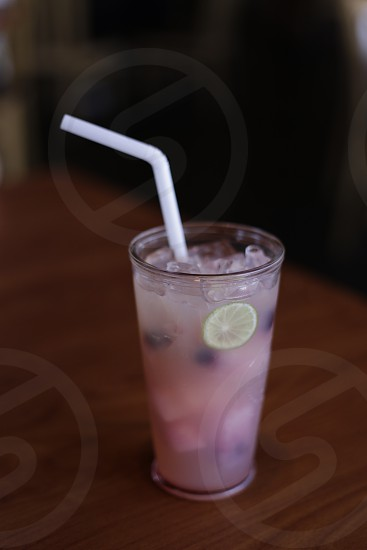 isolated close up shot of refreshing iced chilled pink frozen fruits drink served on a table photo
