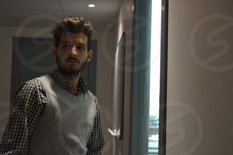 man wearing gray v-neck vest and black and white checkered long-sleeved shirt standing near glass window photo