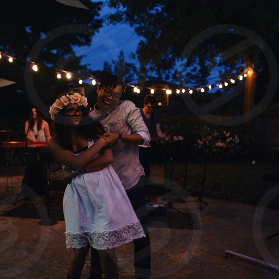 man in white button down long sleeve shirt and black pants dancing with a woman in white dress and pink floral crown photo