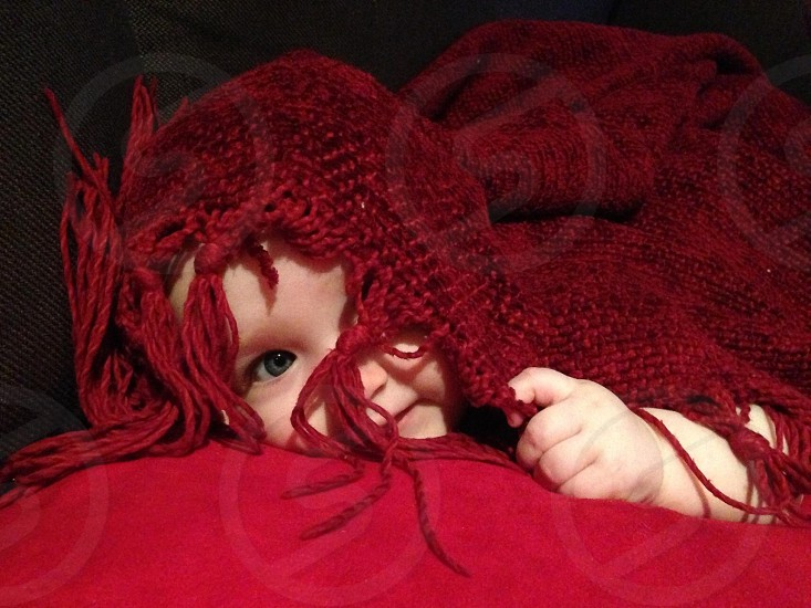baby on couch with red blanket photo