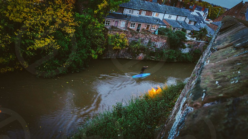 photo of a man in a blue kayak on the river near gray stone walls and white gray houses during gloomy daytime photo